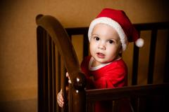 Kid dressed as Santa Claus stands in crib Stock Photos