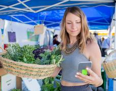 Woman at fruit and vegetable stall holding basket of fresh herbs looking at Stock Photos
