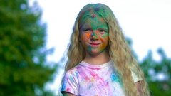 Portrait of cute blonde little girl after a holy powder battle Stock Footage