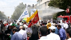 Fire fighters spray water on crowd of people to cool demonstrators in Quds day Stock Footage
