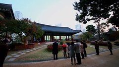 People stand near edifice of Bongeunsa temple and listen sound of drums beat Stock Footage