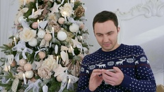 Happy young man in Christmas knitwear sending messages via his phone Stock Footage