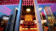 Believers pray behind glass doors of Bongeunsa temple Stock Footage