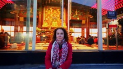 Woman (with model release) sits near glass door of Bongeunsa temple Stock Footage