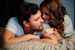 Young sexy couple in love lying in bed in hotel, embracing on white sheets Stock Photos