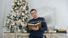 Young man reading aloud from a book standing next to the Christmas tree Stock Footage