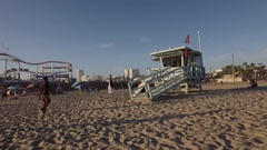 Lifeguard house and Ferris wheel in Santa Monica Beach Stock Footage