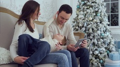 Little boy lying on mothers lap and distracting his father from tablet Stock Footage