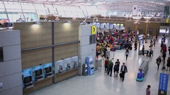 People walk by hall near waiting space with many travelers in Inchhon airport Stock Footage