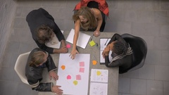 A diverse group of millennials celebrate success at a meeting - overhead slowmo Stock Footage