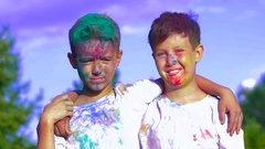 Two boys being attacked with holy powder in front of the camera Stock Footage