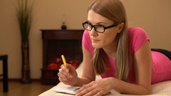 Beautiful attractive young woman writing in notebook. Making a list, thinking Stock Footage
