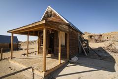 Abandoned ghost town home or shack in the Nevada Desert under clear blue skie Stock Photos