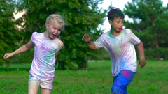Group of children having fun in the park on a sunny warm day chasing each other Stock Footage