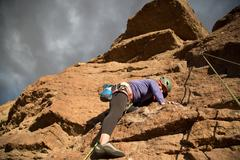 Female rock climber climbing mountain, low angle view, Smith Rock State Park, Kuvituskuvat