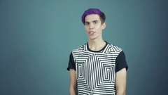 Young video blogger with purple hair talking something in web studio gray Stock Footage
