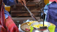 Woman boils silkworm cocoons and makes a silk thread. Traditional asian fabric Stock Footage