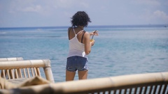 A girl with short hair, a T-shirt and denim shorts stands near the seaside on Stock Footage