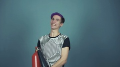 Young video blogger with fire extinguisher in hands laughing in studio gray Stock Footage