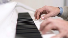 Male hands playing on white piano. Slow motion 120 fps Stock Footage