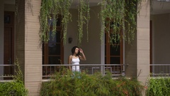 Beautiful dark-haired girl in a white t-shirt slowly out onto the balcony of her Stock Footage