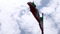 Flag of Islamic republic of Iran waving in wind blue sky clouds in background Stock Footage