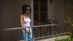 Funny girl in glasses on the porch outside his hotel room. It comes in a great Stock Footage