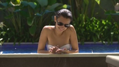 The girl in the pool. She is in a white bathing suit and dark glasses. She Stock Footage