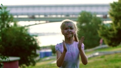 Portrait of happy smiling girl in city park jumping, turning around and clapping Stock Footage