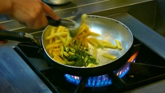 4K footage closeup: cooking - fresh spaghetti stir fried in frying pan Stock Footage