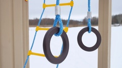 Children playground gymnastic rings swing, snow winter landscape a Stock Footage