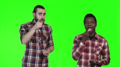 Two men eating french fries on green screen Stock Footage