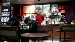 Close up people buying coffee and couple using cellphone inside Starbucks store Stock Footage