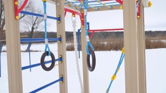 Children playground gymnastic rings swing, snow landscape a winter Stock Footage