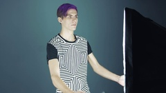 Young angry blogger with purple hair crashing lightbox in web studio gray Stock Footage