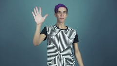 Young pleased blogger with purple hair says HELLO studio gray background Stock Footage