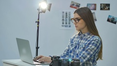 Female photographer working in her professional photo studio with a laptop Stock Footage
