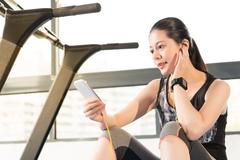 Beautiful asian woman running treadmill use smartphone listening music Stock Photos