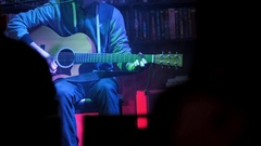 Guitarist plays acoustic guitar in night club, close up Stock Footage