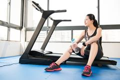 Sport woman rest on treadmill use smartwatch drinking water Stock Photos