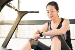 Asian woman sitting on treadmill. smartwatch check pulse rate Stock Photos