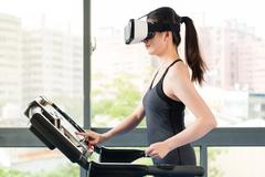 Beauty asian woman running treadmill by VR headset glasses Stock Photos