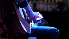Musician in night club - guitarist plays rock acoustic guitar Stock Footage
