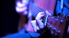 Musician in night club guitarist plays acoustic guitar, extremely close up Stock Footage
