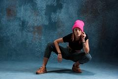 Young girl break dancing on wall background Stock Photos