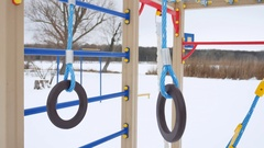 Children playground gymnastic rings swing, winter snow landscape Stock Footage