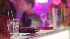 Cocktail glasses on a bar with talking people around. Stock Footage