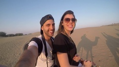 Couple taking a selfie in a camel riding in desert Stock Footage