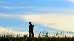 Silly dance of funny child outdoors over golden twilight sky. Arkistovideo