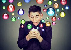 Shocked man using smartphone application icons flying out of cellphone Stock Photos